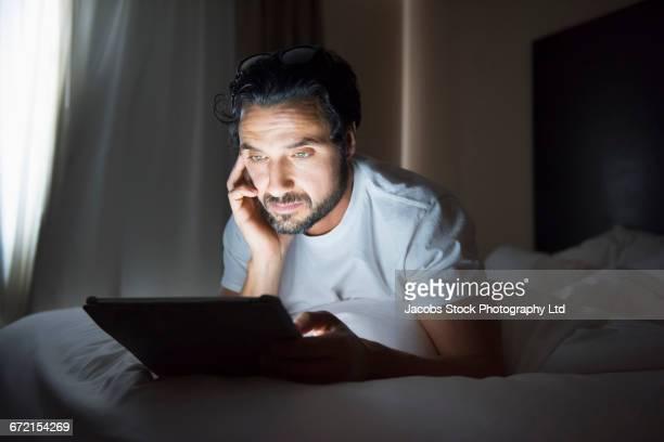 Hispanic man using digital tablet in bed at night