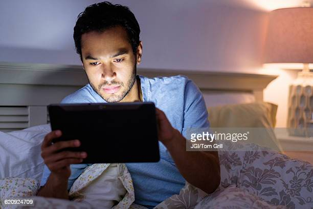 Hispanic man using digital tablet in bed