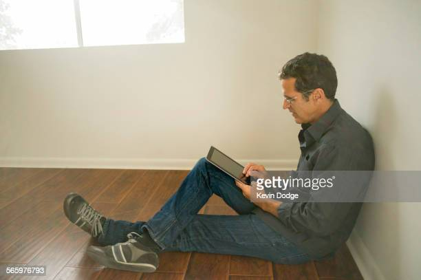 hispanic man using digital tablet on floor of empty room - endast medelålders män bildbanksfoton och bilder