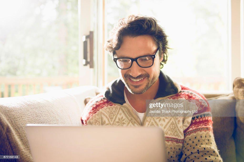 Hispanic man using laptop on livingroom sofa : Stock Photo