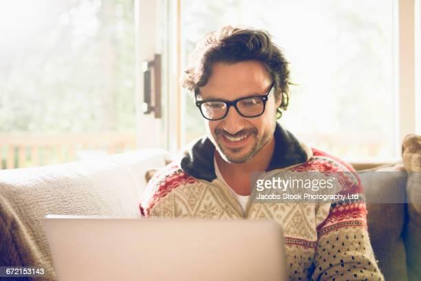 Hispanic man using laptop on livingroom sofa
