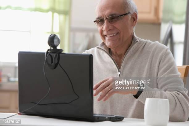 Hispanic man using laptop webcam in kitchen