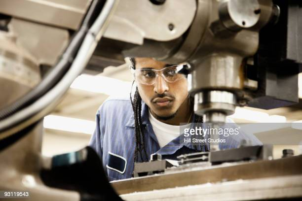 hispanic man using machine in machine shop - community college stock pictures, royalty-free photos & images