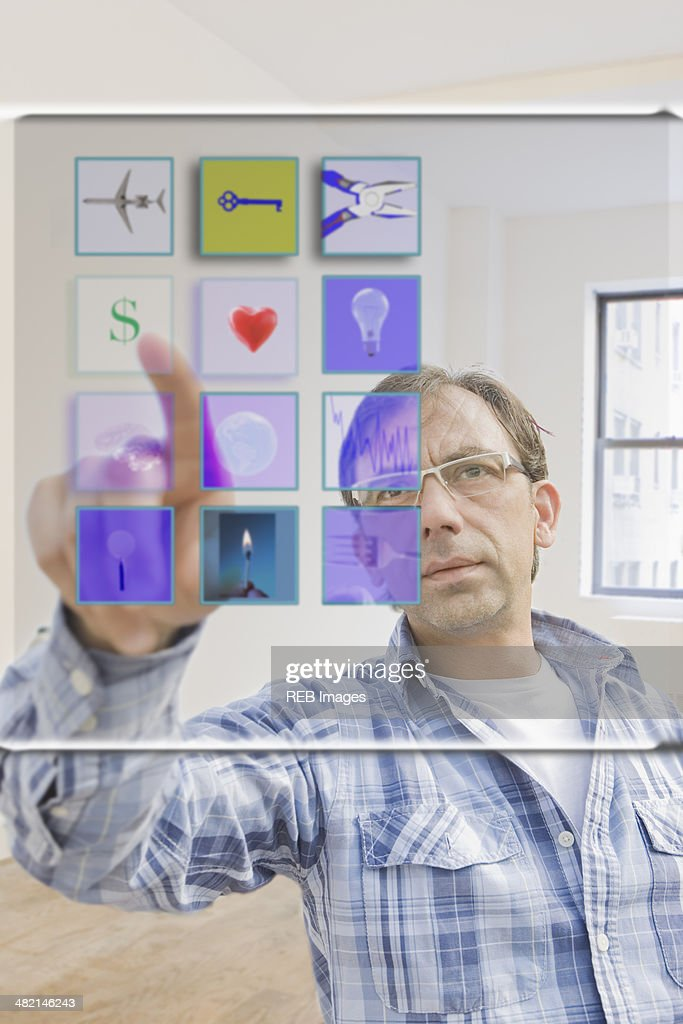 Hispanic man using mobile apps on virtual screen : Stock Photo