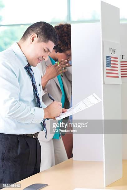 hispanique homme voix dans la cabine de vote - voter registration photos et images de collection