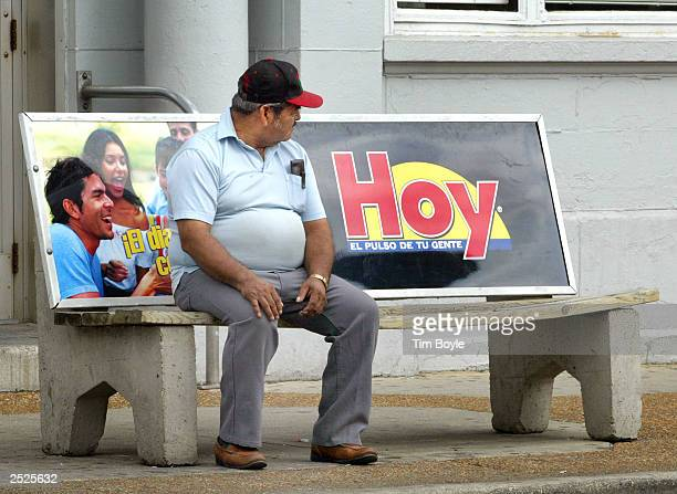 Hispanic man waits for a bus sitting on a bench with an Hoy newspaper ad September 22 2003 in Chicago's mainly Hispanic Little Village neighborhood...
