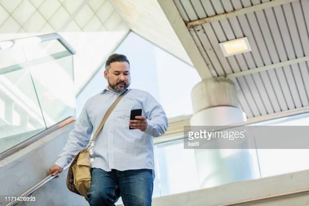 hispanic man walking, looking at mobile phone - large build stock pictures, royalty-free photos & images