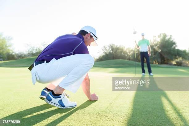 Hispanic man watching friend crouching on golf course