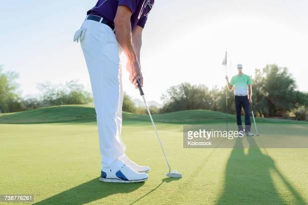 Hispanic man watching friend putting on golf course