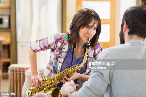 Hispanic man watching girlfriend playing saxophone