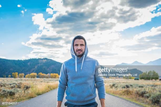 Hispanic man wearing hooded sweatshirt near mountain