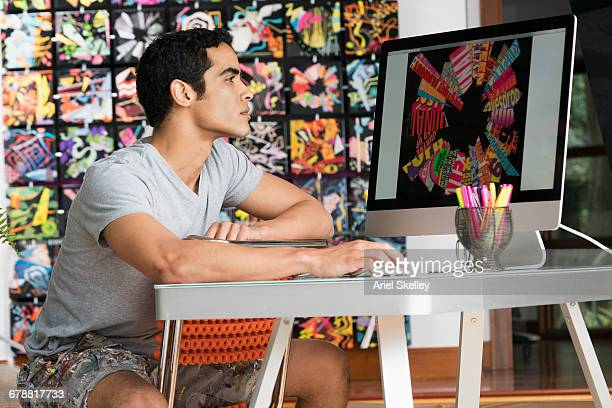 hispanic man wearing shorts using computer in art studio - desenhista gráfica - fotografias e filmes do acervo