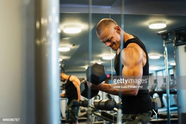 hispanic man weightlifting in gymnasium - bodybuilding stock-fotos und bilder