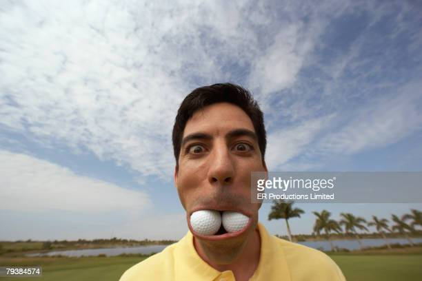 hispanic man with golf balls in mouth - golf humour photos et images de collection