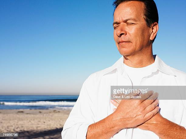 Hispanic man with hands over heart at beach