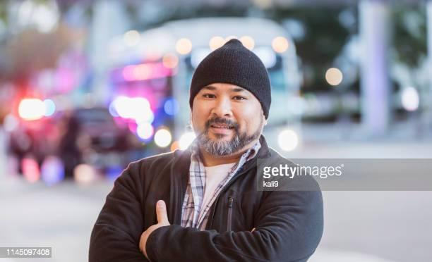 Hispanic man with knit hat standing on city street