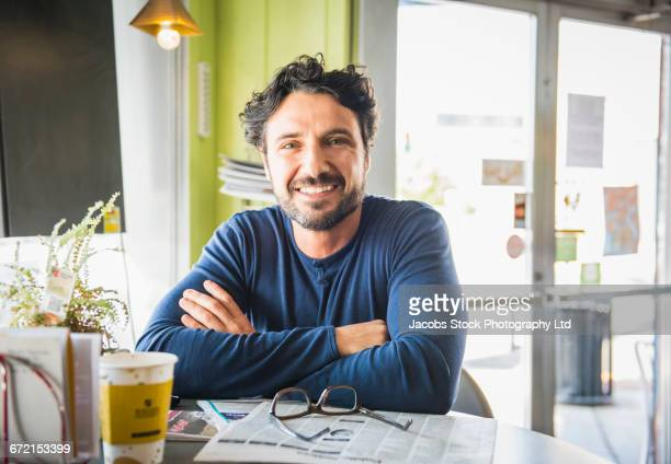 Hispanic man with newspaper posing in coffee shop