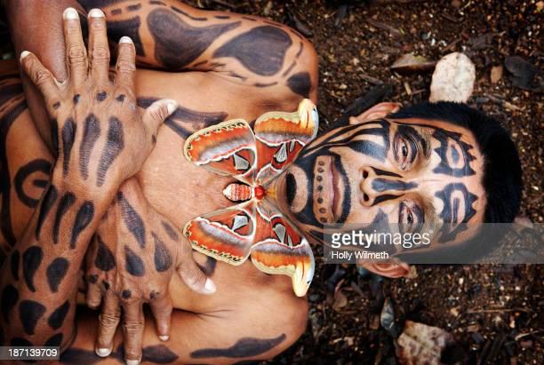 Hispanic man with painted body laying in dirt, Lago Izabal, Guatemala