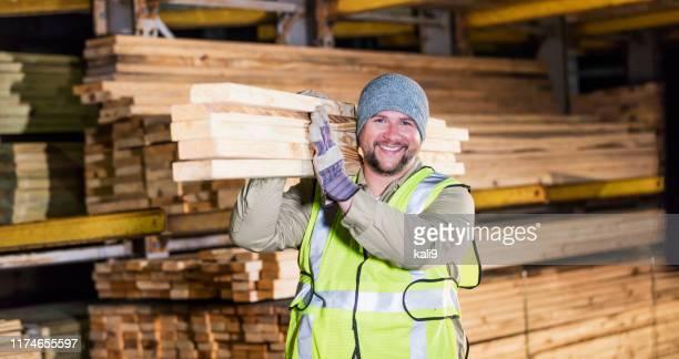 hispanic man working at lumber yard - carrying stock pictures, royalty-free photos & images