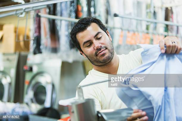 hispanic man working in a dry cleaner - dry cleaner stock pictures, royalty-free photos & images