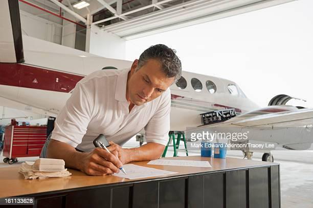 Hispanic man working in airplane hangar