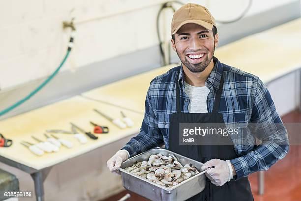 Hispanic man working in seafood market, carrying shrimp