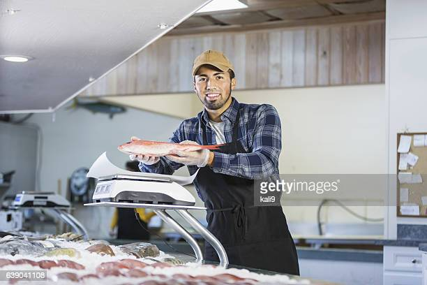 Hispanic man working in seafood market, holding fish