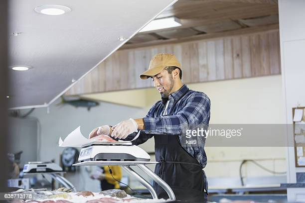 Hispanic man working in seafood market, weighing fish