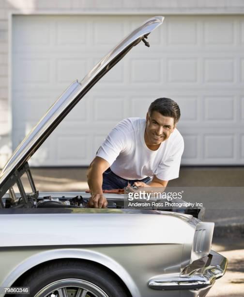 Hispanic man working under hood of car