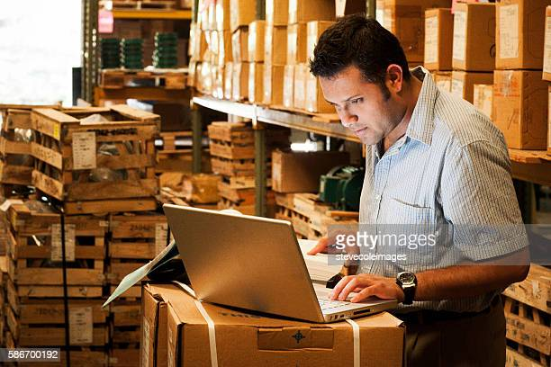 hispanic manager in warehouse - heavy industry stock photos and pictures