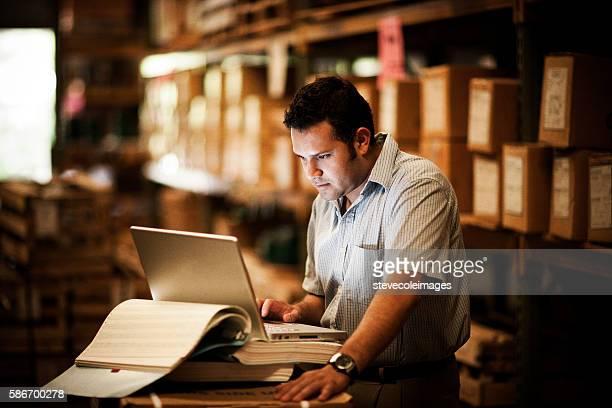 hispanic manager in warehouse - lista de chequeo fotografías e imágenes de stock