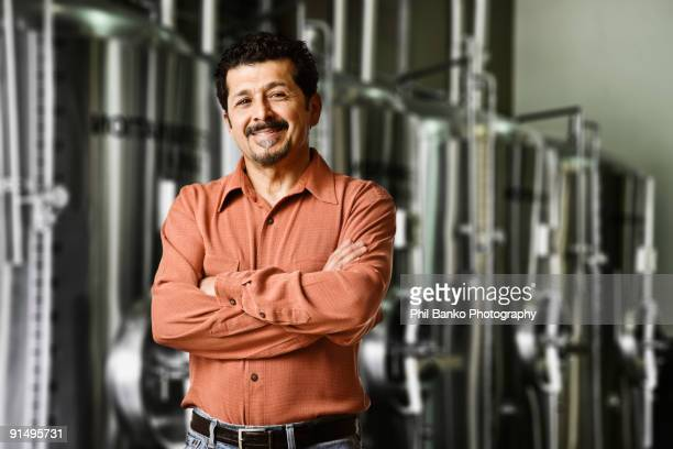 Hispanic manager standing near vats in factory