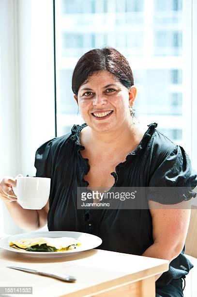 Hispanic mature woman having breakfast