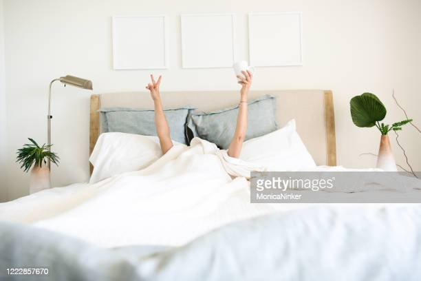 hispanic mature woman waking up in bed with coffee mug in hand - comfortable stock pictures, royalty-free photos & images