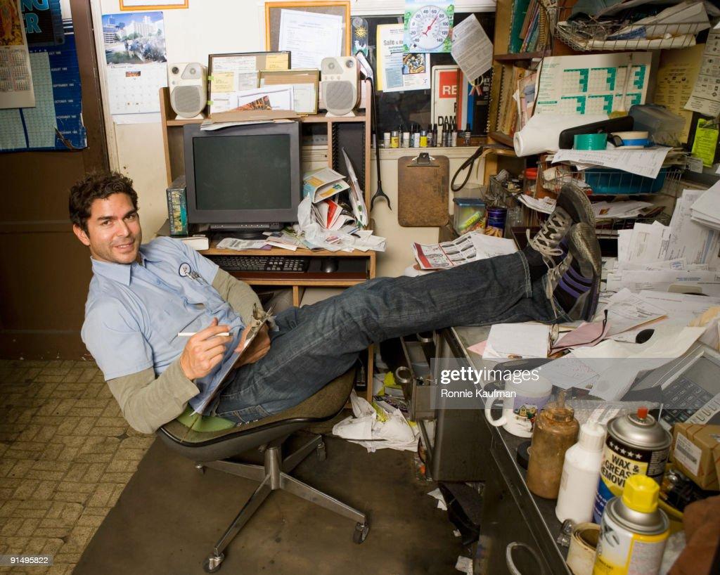 Hispanic Mechanic In Garage Office : Stock Photo