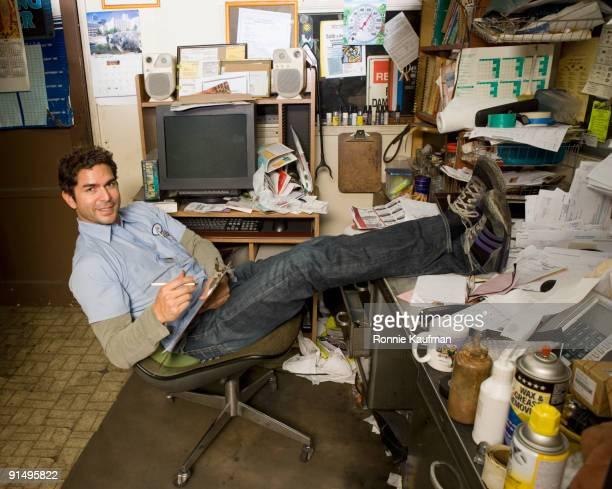 Hispanic mechanic in garage office