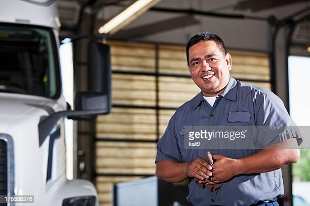 Hispanic mechanic in garage with truck