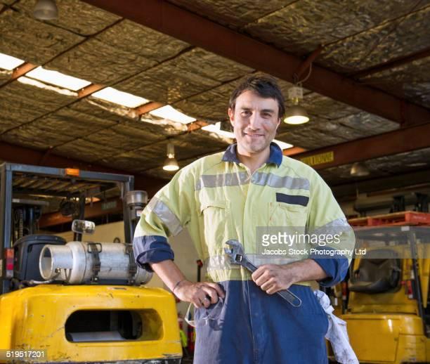 Hispanic mechanic smiling in warehouse