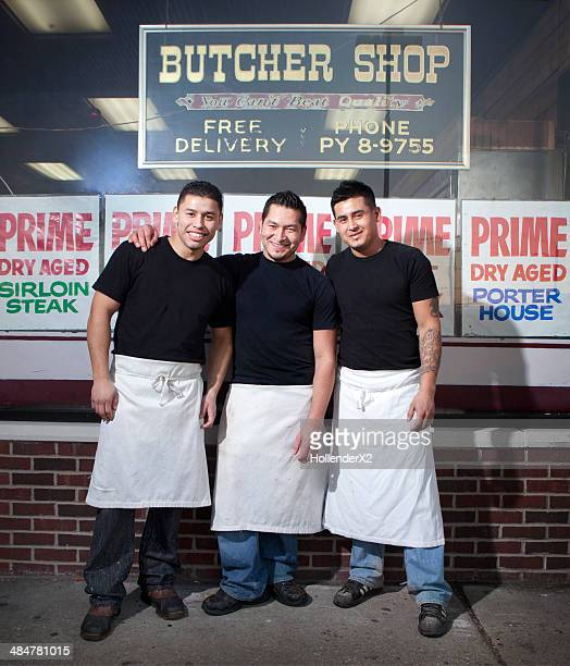 3 hispanic men in front of their butcher shop
