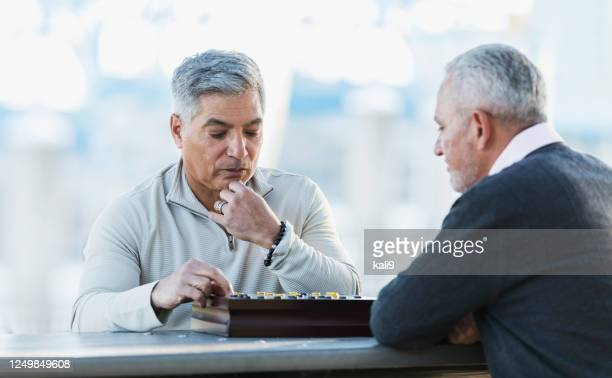 hispanic men playing a game of checkers - chequers stock pictures, royalty-free photos & images