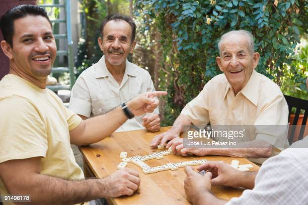 Hispanic men playing dominos on patio