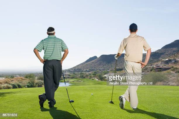 hispanic men playing golf - hand on hip stock pictures, royalty-free photos & images