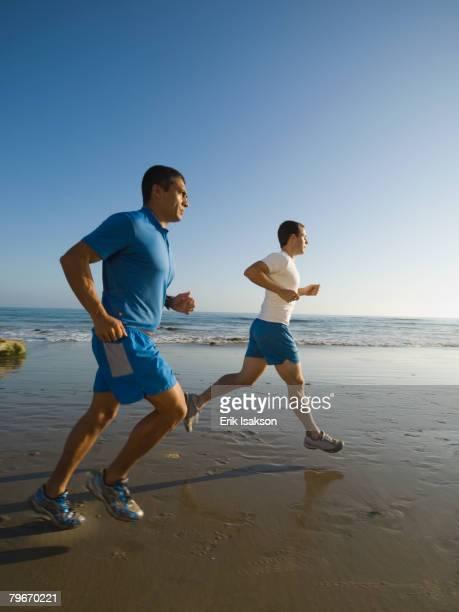 Hispanic men running at beach