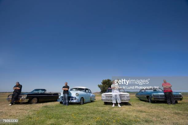 hispanic men standing in front of low rider cars - low rider stock pictures, royalty-free photos & images