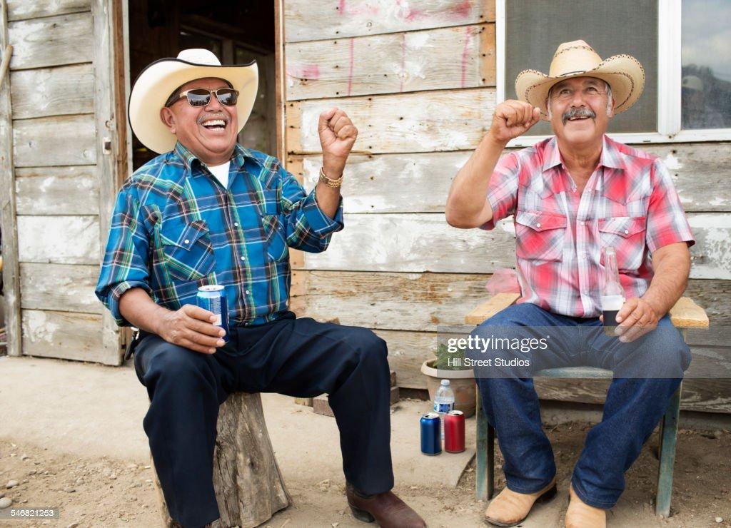 Hispanic men wearing cowboy hats cheering : Stock Photo