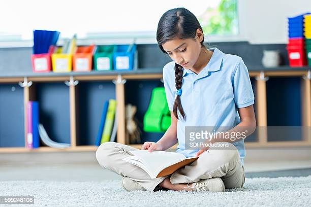 hispanic middle school student reads book in classroom - charter_school stock pictures, royalty-free photos & images