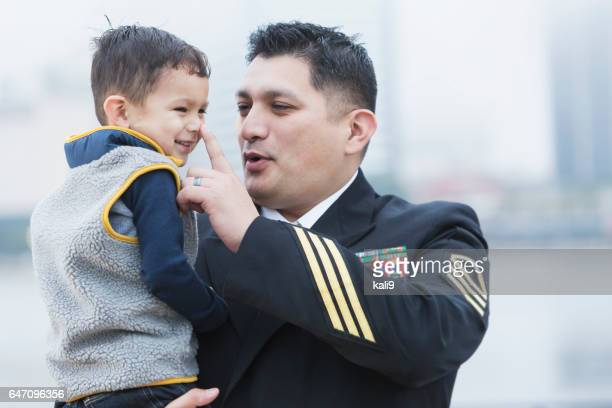 hispanic military man holding 2 year old son - navy stock pictures, royalty-free photos & images