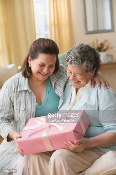Hispanic mother and adult daughter exchanging gift