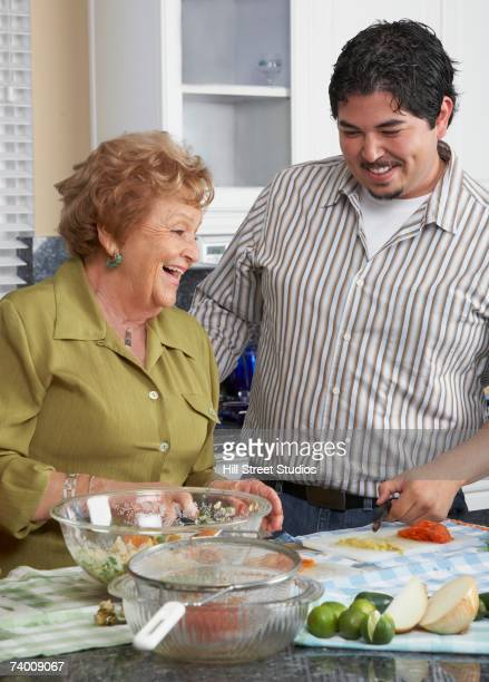 Hispanic mother and adult son preparing food