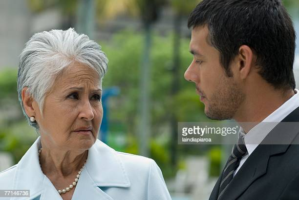 Hispanic mother and adult son talking